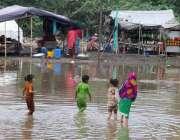 فیصل آباد: خانہ بدوش بچے بارش کے جمع شدہ پانی میں نہا رہے ہیں۔