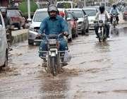 راولپنڈی: موٹر سائیکل سوار بارش کے جمع شدہ پانی سے گزر رہے ہیں۔