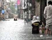 راولپنڈی: شہر میں ہونے والی موسلا دھار بارش کے بعد شہری جمع شدہ پانی ..