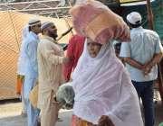لاہور: ایک خاتون رمضان بازار سے خریدا سامان اپنے سر پر رکھ کر لیجا رہی ..
