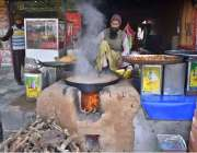 فیصل آباد: دکاندار گاہکوں کو متوجہ کرنے کے لیے پکوڑے بنارہا ہے۔