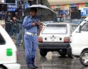 راولپنڈی شہر میں ہونیوالی بارش کے دوران ٹریفک وارڈن چھتری تا نے اپنی ..