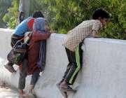 راولپنڈی: مری روڈ پر بچے خطرناک انداز سے دیوار پر لٹک کر نالہ لئی کی ..