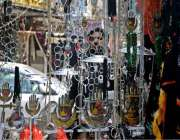 راولپنڈی:عزادار ایک دکان سے علم وتعزیے سے دیکھ رہے ہیں۔