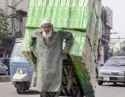 لاہور: ایک معمر محنت کش گھر کی کفالت کے لیے ہتھ ریڑھی پر سامان رکھے لیجا ..