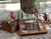 ملتان: معمر محنت کش دوپہر کے وقت درخت کے سائے میں آرام کر رہا ہے۔