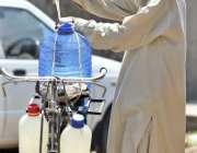 راولپنڈی: ایک معمر شخص پینے کے لیے صاف پانی کے کین سائیکل پر لوڈ کر رہا ..