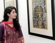 لاہور: الحمرا ہال قذافی سٹیڈیم میں ایک لڑکی پینٹنگ دیکھ رہی ہے۔