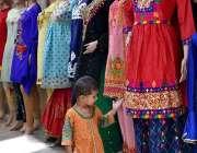 لاڑکانہ: خانہ بدوش بچی کی دکھان پر رکھے گئے کپڑوں میں دلچسپی۔