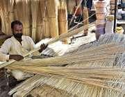 فیصل آباد: کارکن اپنے سڑک کنارے روایتی جھاڑو بنانے میں مصروف ہے۔