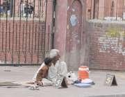 لاہور: ایک محنت کش بزرگ سڑک کنارے وزن چیک کرنے والی مشین رکھے گاہکوں ..