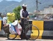 اسلام آباد: محنت کش اپنی سائیکل پر ردی جمع کرنے کے بعد واپس جا رہا ہے۔