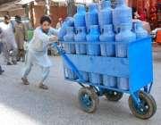 راولپنڈی: ایک شخص مقامی مارکیٹ میں پینے کے پانی سے بھری کین فروخت کر ..