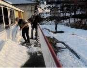 مری: برفباری کے بعد مکین گھر کے آگے سے برف ہٹا رہے ہیں۔