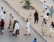 راولپنڈی: عید پر اپنے آبائی علاقوں کو جانے والے مسافر سڑک کراس کر رہے ..