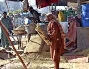 فیصل آباد: مونگ پھلی کی صفائی میں مصروف ایک خاتون کارکن