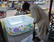 فیصل آباد: دکاندار گاہکوں کو متوجہ کرنے کے لیے بچوں کے سوئمنگ پول میں ..