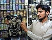 لاڑکانہ: دکاندار گاہکوں کو متوجہ کرنے کے لیے جیولری سجا رہا ہے۔