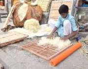 لاہور: ایک محنت کش لڑکا ائیرکولرز کی خسیں تیار کررہا ہے۔