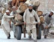 راولپنڈی: مزدور ہتھ ریڑھی پر بھاری لکڑی رکھے لیجا رہے ہیں۔