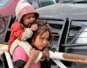 راولپنڈی: ننھی بچی اپنی بہن کو کندھے پر بٹھائے جار ہی ہے۔