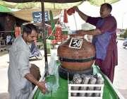 فیصل آباد: ریڑھی بان گاہکوں کو متوجہ کرنے کے لیے لسی بنا رہا ہے۔