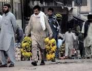 راولپنڈی: فروڈ منڈی میں ایک شہری بیوپاریوں سے کیلے خرید رکر لیجا رہا ..