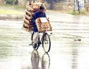 لاہور: ایک محنت کش بارش کے دوران سائیکل پر لکڑی کی چوکیاں فروخت کے لئے ..