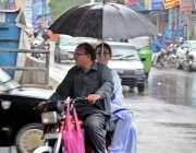 راولپنڈی: موٹر سائیکل سوار طالبہ نے بارش سے بچنے کے لیے چھتری تان رکھی ..