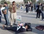 لاہور: پیرا میڈیکل سٹاف کے مال روڈ پر دھرنے کے دوران ایک شخص سڑک پر لیٹا ..