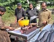 اسلام آباد: ایک دکاندار سڑک کنارے صارفین کو راغب کرنے کے لئے مچھلیاں ..