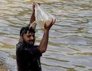 لاہور: ایک شہری نہر کنارے گرمی کی شدت کم کرنے کے لیے اپنے اوپر پانی ڈال ..