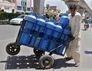 راولپنڈی: محنت کش ہتھ ریڑھی پر پینے والے پانی کے کین رکھے سپلائی کے ..