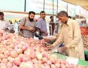 لاہور:شہری شادمان سستے رمضان بازار میں ایک سٹال سے پیاز خرید رہے ہیں۔