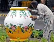 راولپنڈی: پی ایچ کا اہلکار سبزہ زار میں رکھے گئے ایک بڑے گملے کو پینٹ ..
