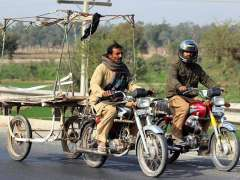 MULTAN: A motorcyclist on the way while pushcart attached with it.