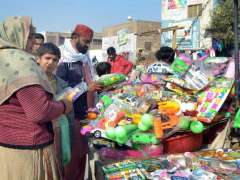 MULTAN: Devotees busy in selecting and purchasing toys form roadside vendor.