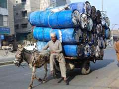 FAISALABAD: A donkey driven cart on the way loaded with empty containers at Sargodha Road.