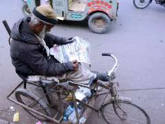 KARACHI:A man with disability reads a newspaper on his tri-cycle along the roadside.