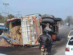 ISLAMABAD: A view of heavy loaded truck flipped over at Express Way.