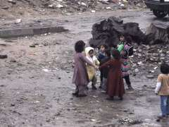 ISLAMABAD: Gypsy children playing outside their makeshift huts during rain at slum area in the federal capital.