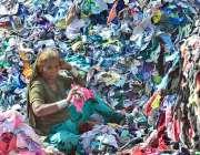 حیدرآباد: ایک بزرگ مزدور خاتون گودام میں کپڑوں کے ٹکڑوں کو چھانٹ رہی ..