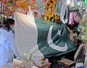 راولپنڈی: راجہ بازار میں ایک شہری 14 اگست کے حوالے سے بڑے سائز کا جھنڈا ..