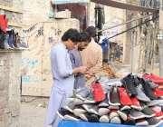 لاہور، مزنگ روڈ پر ایک محنت کش نے گرم بوٹ فروخت کیلئے سجا رکھے ہیں۔