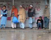 راولپنڈی، بارش کے دوران مزدور مزدوری کی تلاش میں کھڑے ہیں۔