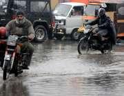 راولپنڈی: موٹر سائیکل سوار دن بھر جاری رہنے والی بارش کے باعث کھڑے پانی ..