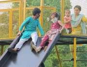 لاہور : باغ جناح میں آنے والے بچے سلائیڈ لے رہے ہیں۔