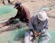 کراچی، مچھرے مچھلی کا جال بنا رہے ہیں۔