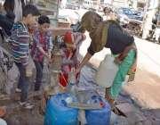 کراچی: ایک خاتون بچوں کیساتھ رنچور لائن میں پبلک ہینڈ پمپ سے پینے کا ..
