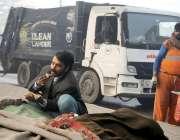 لاہور: ایک شخص کوڑے والی گاڑی کے پاس بیٹھا کھانا کھا رہا ہے۔